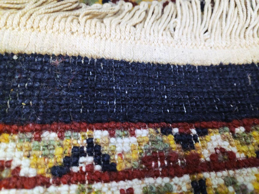 The back of a machine-made rug with a fringe sewn onto it. Image by Velvet.