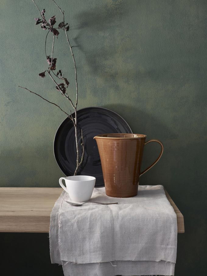 Ceramics: a black platter, a jug and a mug on a sideboard. Such simplicity yet looking so elegant. Image by John Lewis.