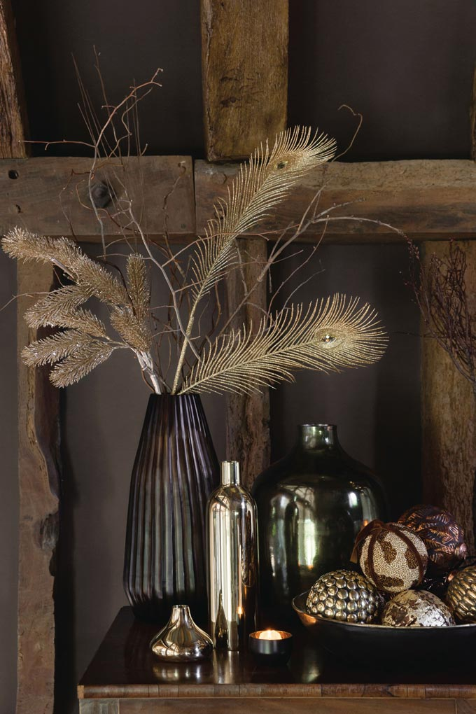 A beautifully styled vase on a sideboard along with other decor, filled with gold sticks and golden peacock feathers.
