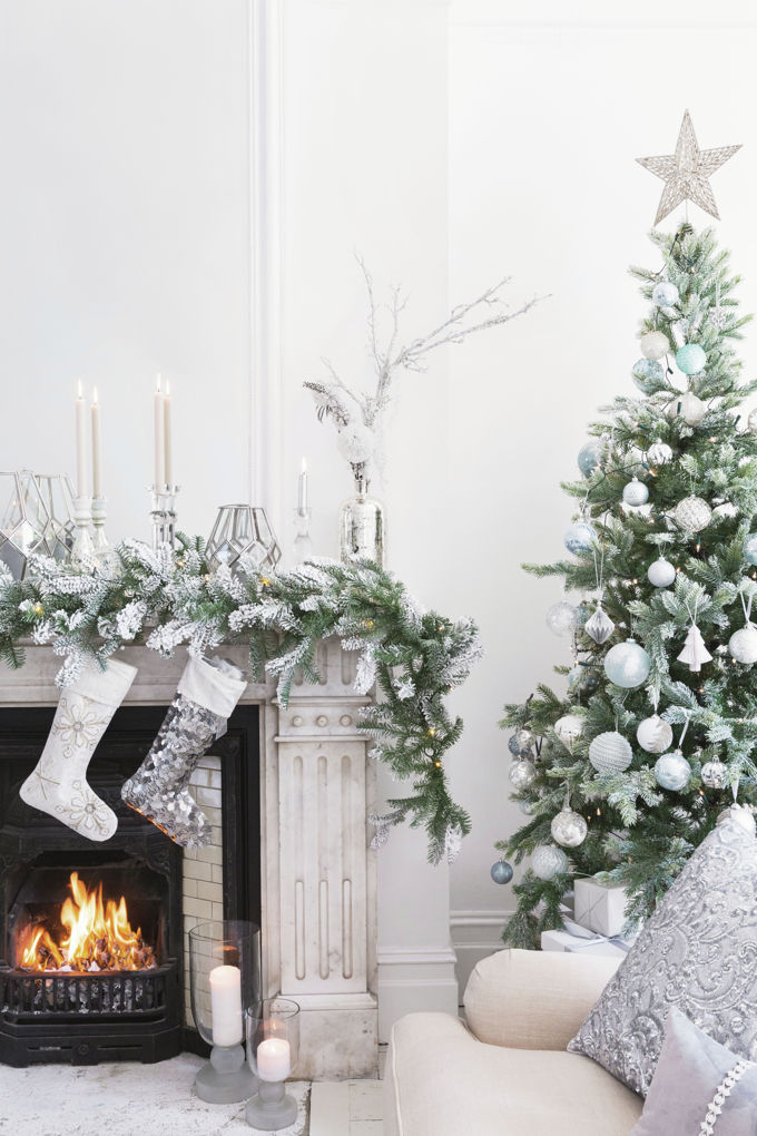 How beautiful. A Christmas tree with white ornaments next to a fireplace with white decor, stockings and a snowy looking garland. Just like Wonderland. Image by Amara.
