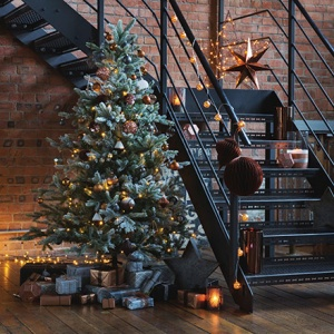 A stunning Christmas tree by a black steel staircase, beautifully decorated. Image by Amara.