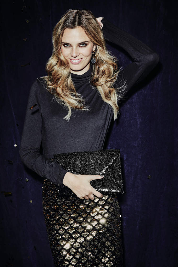 A black silk top combined with a goldish shiny skirt is not a bad combo like in this case. Her blonde hair helps too. Image by Dorothy Perkins.