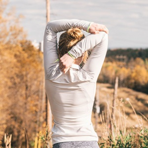 a woman's rear side while she's stretching her arm behind her head somewhere outdoors.
