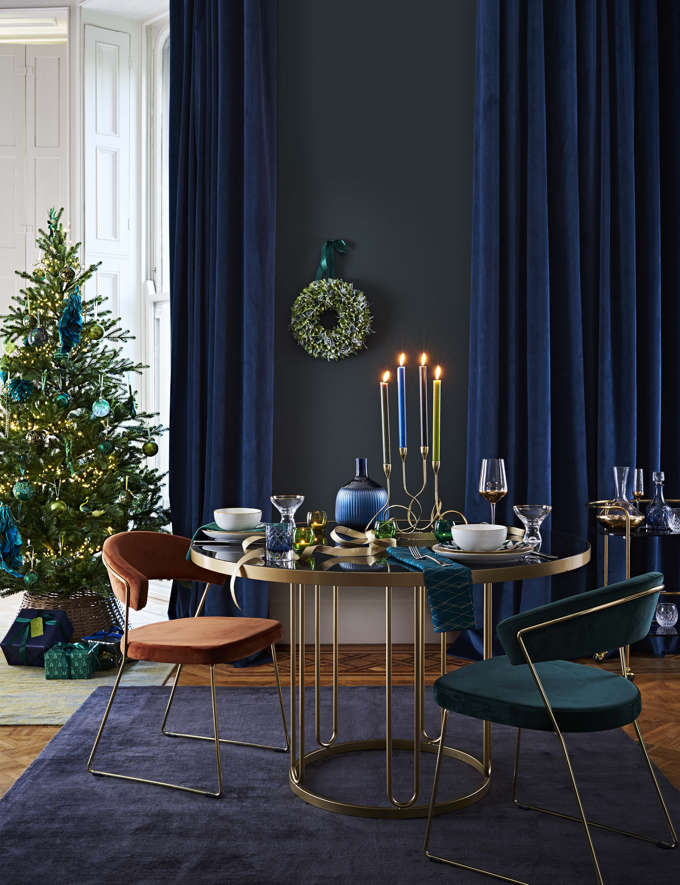 A very elegant dining space with blue and teal hues and with a similar color coordinated ornaments Christmas tree. Image by John Lewis.