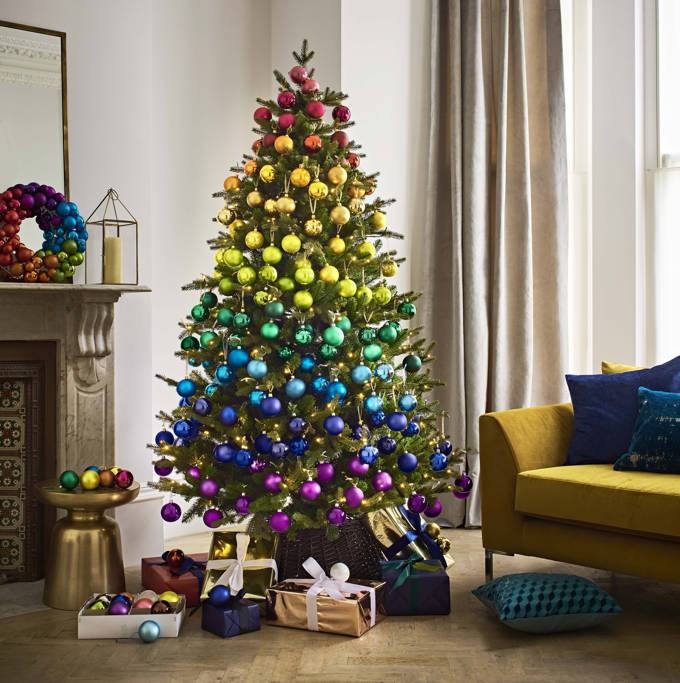 A Christmas tree decorated with lots of baubles in various colors forming a striped rainbow effect. Cool! Image by John Lewis.