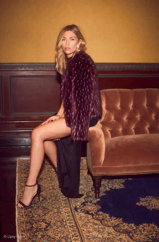 Abbey Clancy wear a burgundy faux fur jacket over a burgundy dress looking smashing. Image by Lipsy.