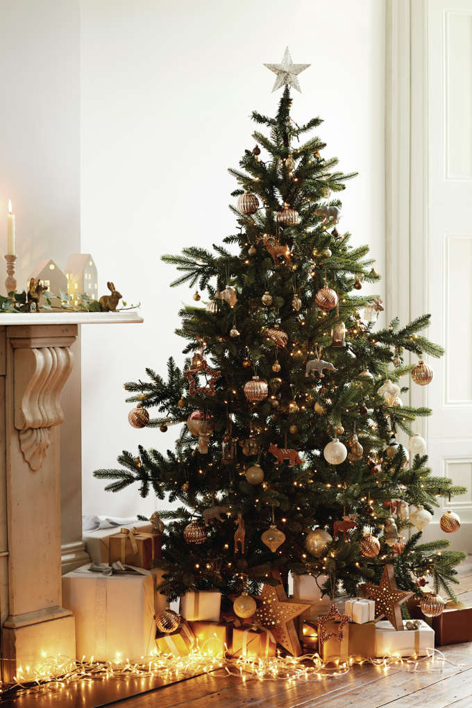 A stunning Christmas tree by a fireplace with copper toned ornaments. Image by Marks & Spencer.