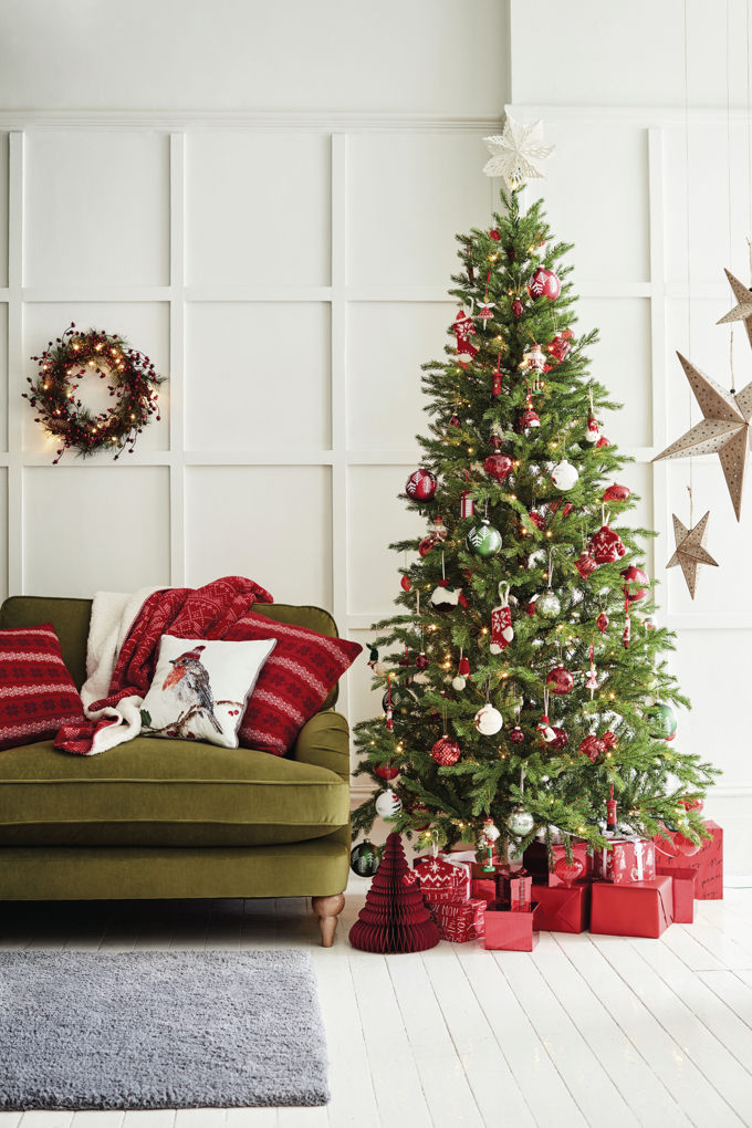 A traditional looking Christmas tree with red and green ornaments besides a green velvet sofa. Love how all the presents are wrapped in red paper. Image by Marks & Spencer.