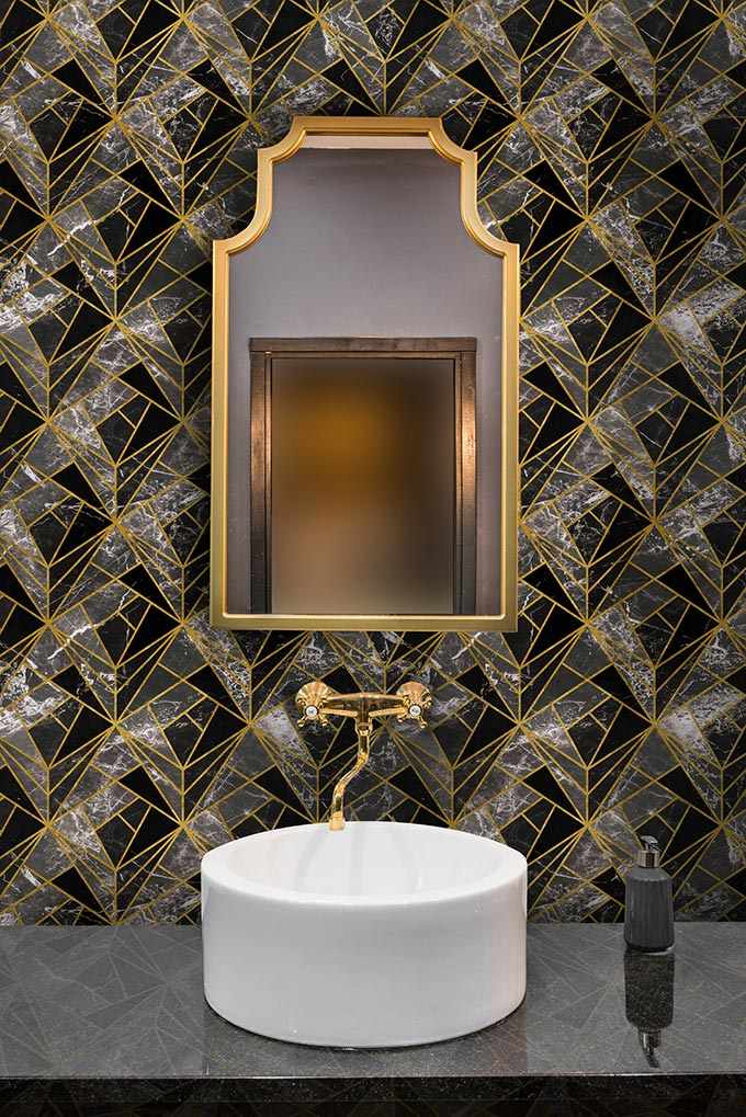 A beautiful geometric pattern wallpaper looks stunning in this bathroom with a vintage looking brass framed mirror over a round washbasin. Image by Mind the Gap.
