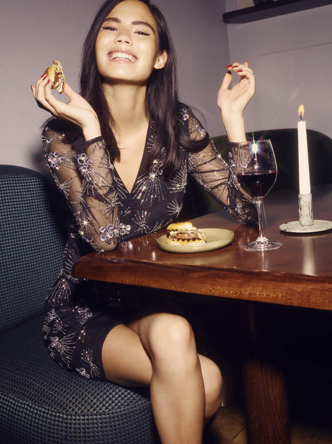 A woman eating a burger in a very elegant party outfit. Image by Miss Selfridge.