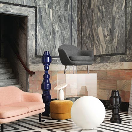 The Normann Copenhagen Eddy table lamp on a mustard colored velvet pouf amongst other furniture including a blush pink two seater sofa. The surrounding walls appear to be made of two different kinds of marble. Image by Nest.co.uk.