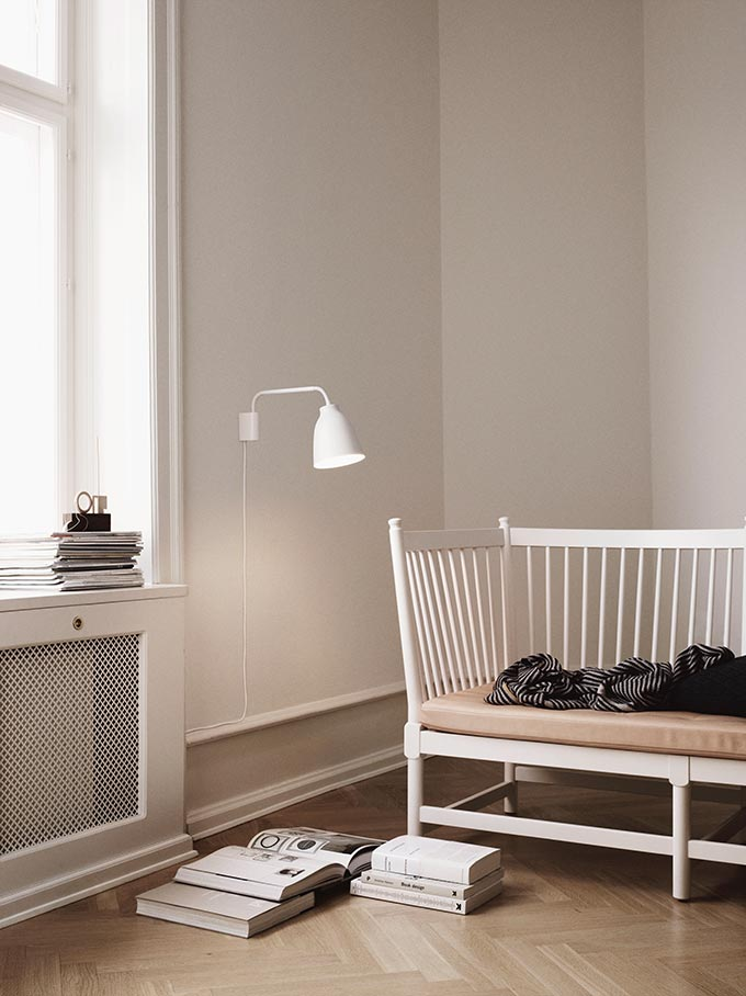 A beige room with a wooden sofa with an accent reading light: Caravaggio Read Wall Light by Lightyears. Image by Nest.co.uk.