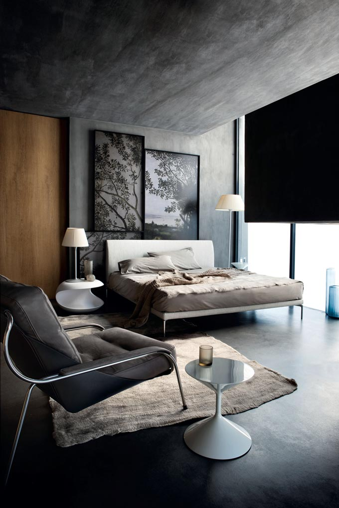 This is a stunning urban chic bedroom with concrete walls, floor and ceiling and large windows from floor to ceiling. The contemporary Zanotta 1883 Talamo bed and armchair complete this minimal setting. Image by Nest.co.uk.