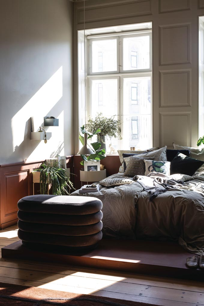 I love this ribbed velvet Ferm Living pouf found in this stylish, warm bedroom with rusty hued panelboards on the walls. Image by Nest.co.uk.
