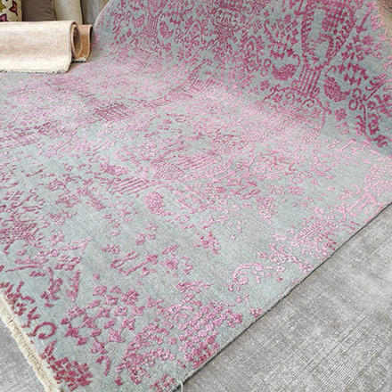 View of a handmade rug in grey and pink hues.