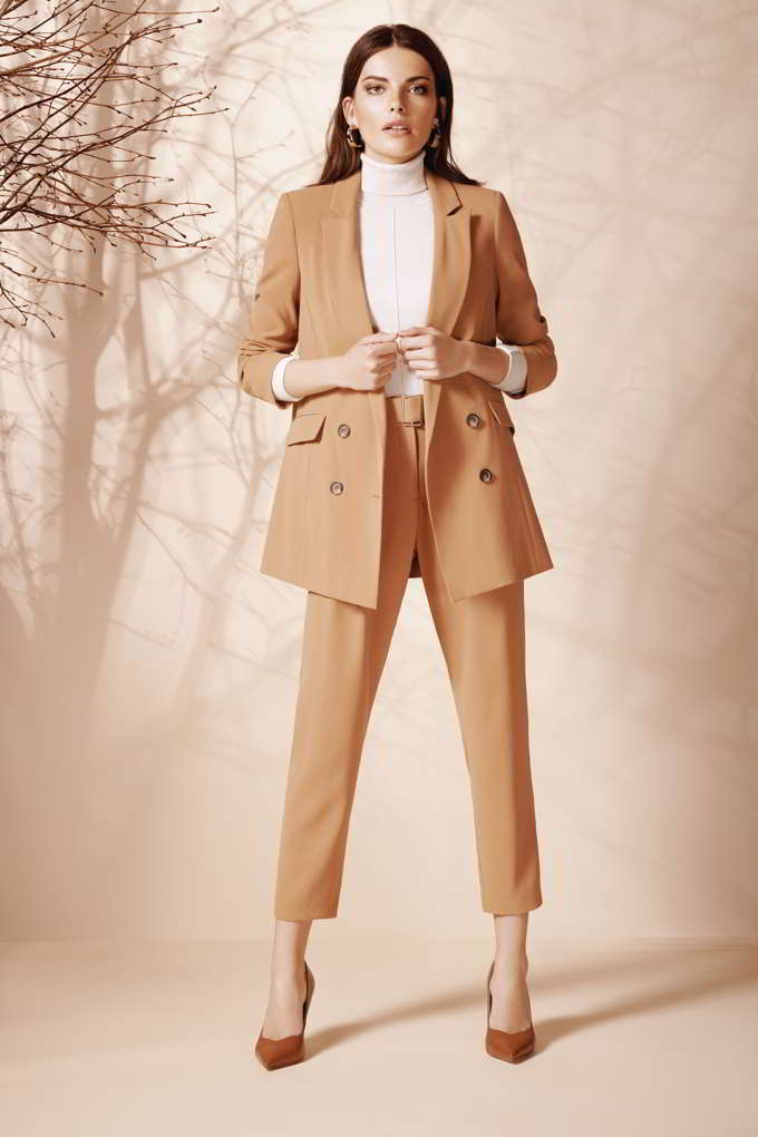 A camel pant suit paired with a white turtleneck and camel pumps always looks so chic. Image by Wallis.