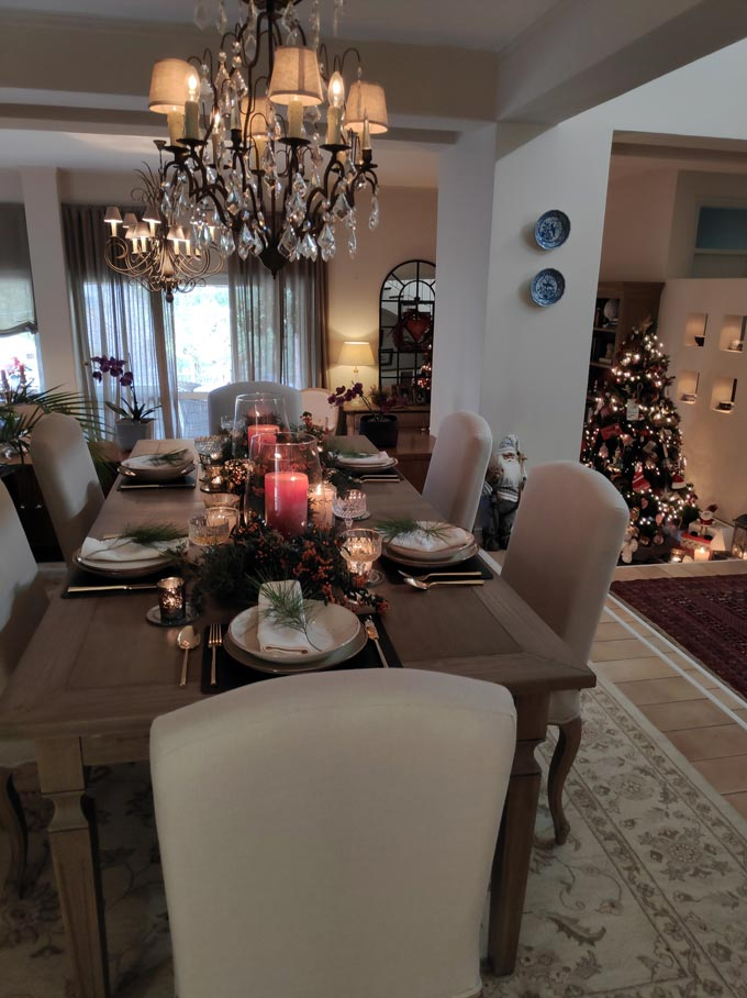 View of Elisabeth's dining table with the Christmas tabletop and partial view of her living room and Christmas tree in the background.