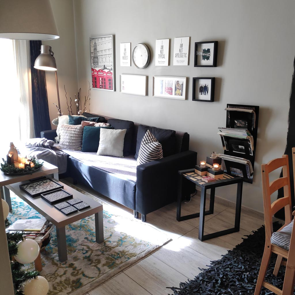 View of Timo's small living room with a black sofa and an art gallery wall.