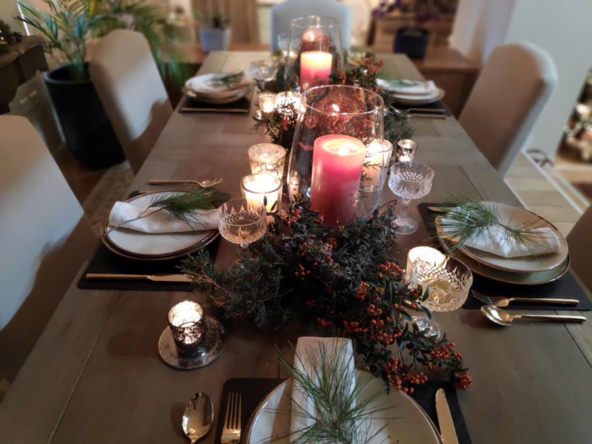 Full view of Elisabeth's Christmas tabletop with two large orange red candles in the middle.