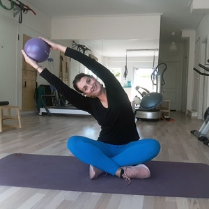 Ifiyenia holding a ball up while seated on a yoga mat just before her ball workout.