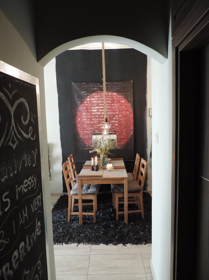 View of the dining space from the corridor with the accent black colored block on the wall and the art image of a brick wall.