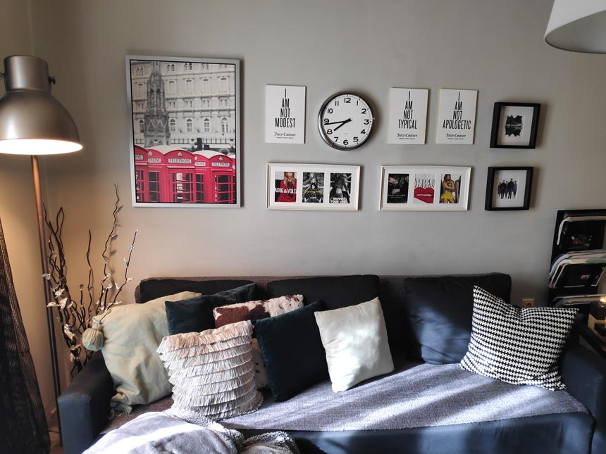 View of the black sofa with its decorative cushions and the art gallery over it that includes a clock.