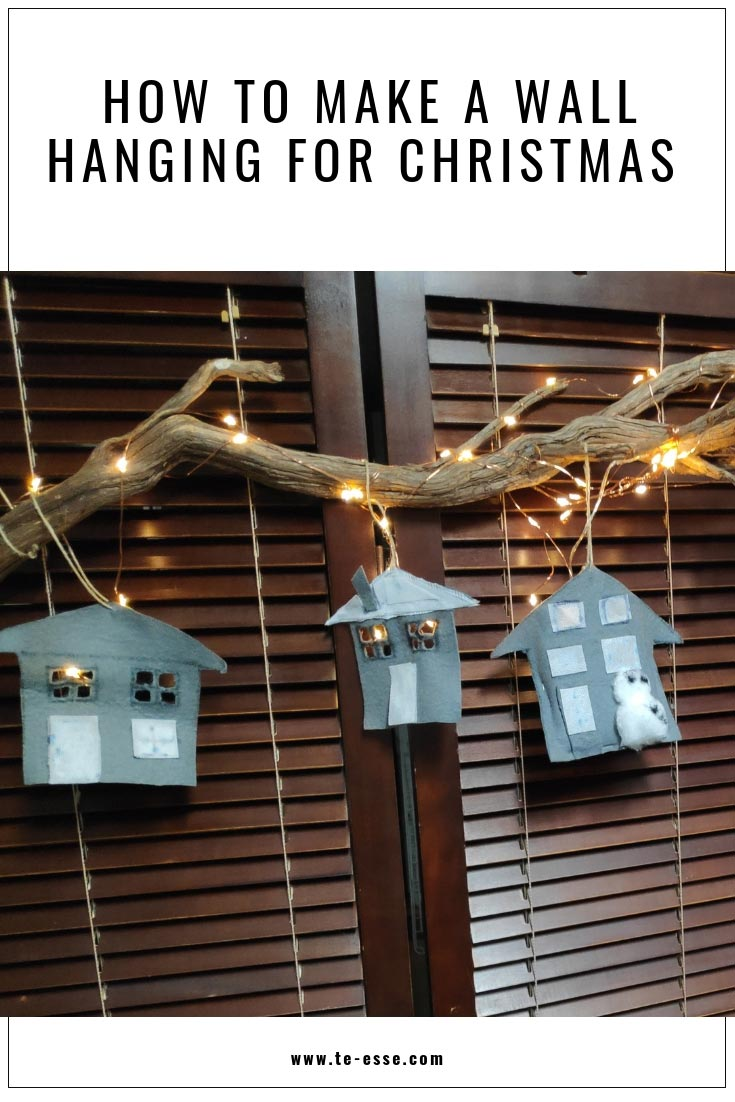 A pin graphic with partial image of the Christmas wall hanging that has lit homes as a theme.