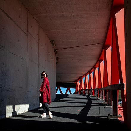 A woman in a red coat standing outdoors under the roof canopy of a concrete building with a steel structure on the side. Image by Artem Gavrysh on Unsplash.