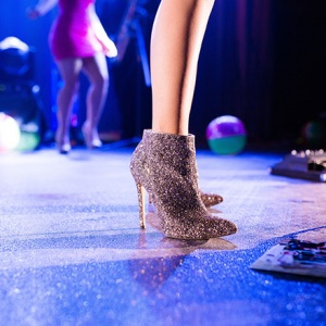 A woman wearing some glittery ankle boots at a party.