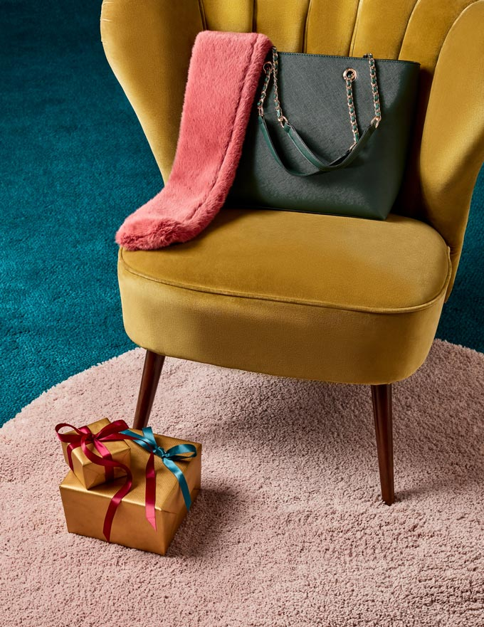 A mustard velvet armchair with a forest green bag atop and a coral scarf seem to fuse really well together colorwise. Image by Dorothy Perkins.
