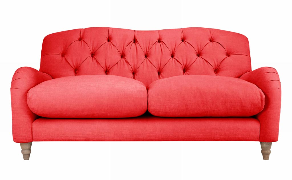 A sofa in a coral color. Image by John Lewis.