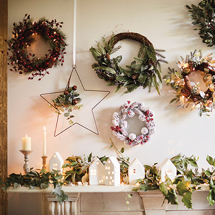 I love a white Christmas village with a garland as decor on a fireplace mantel, but the beautiful wreaths above it are stealing all the glory. Image by Marks & Spencer.