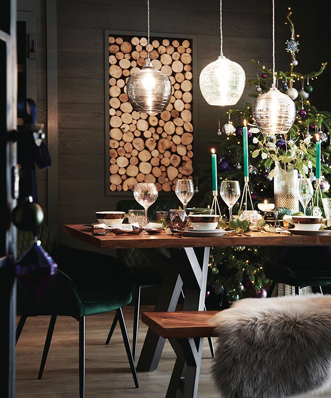 A dark and moody dining space, styled for a festive dinner and a Christmas tree in the background. Simply breathtaking. Image by Next.