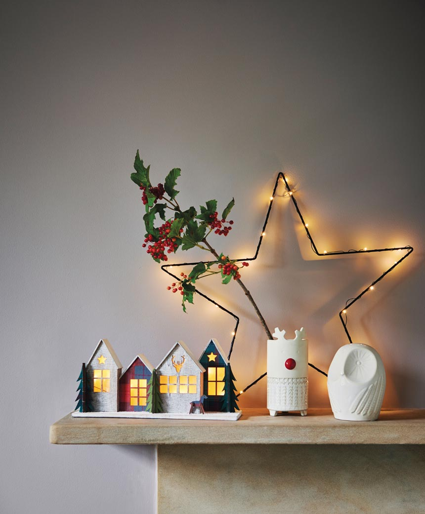 A little wire star as decor upon a mantle along with a Christmas village and a holly berry branch. Image by Next.