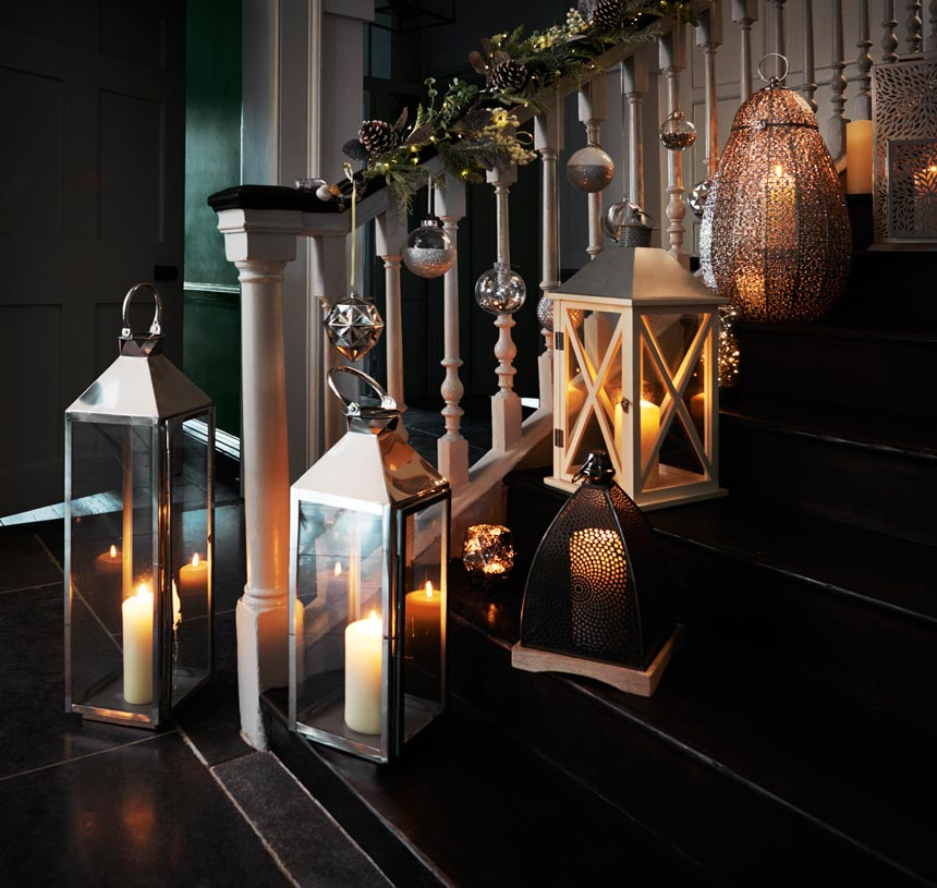A clutter of lanterns along a home staircase with all the candles lit. Image by Next.