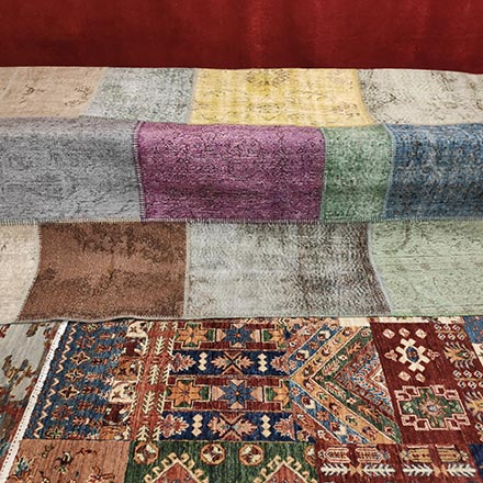 Layers of different colorful area rugs.