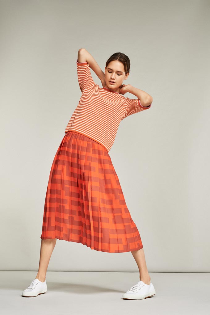 A preppy look with a striped orange tee and a midi orange print skirt paired with white sneakers. Casual but sophisticated. Image by Debenhams.