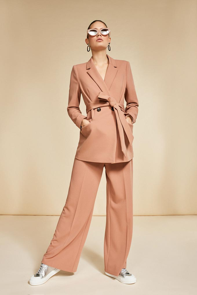 A beige pantsuit with golden kicks here looks very casual and sophisticated. Image by Debenhams.