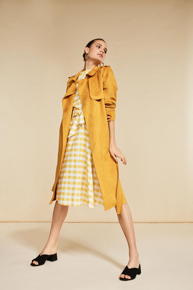 A mustard yellow print dress with a mustard colored trench coat is looking awfully feminine. Image by Debenhams.