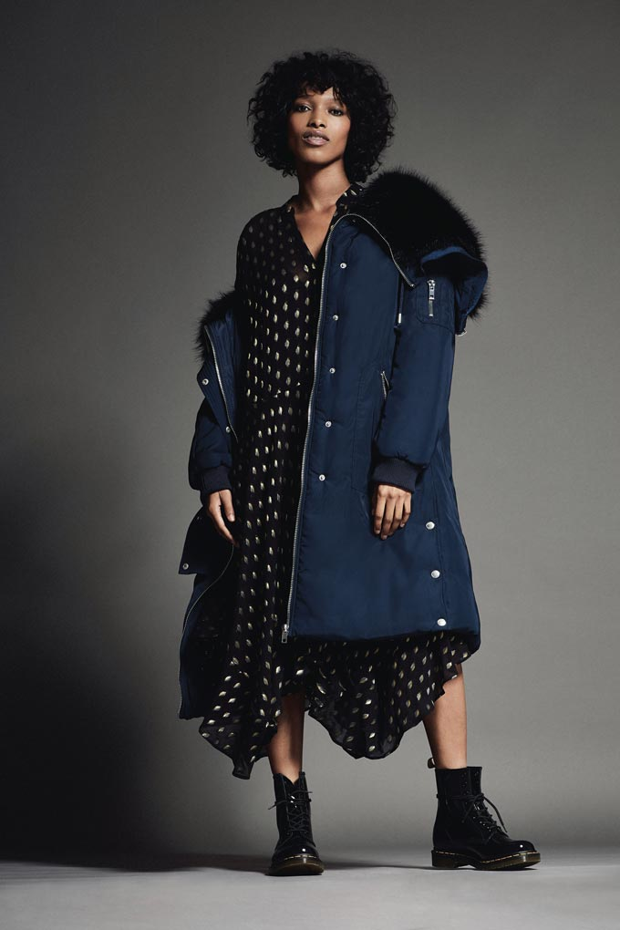 A dark blue jacket with some black fur paired together with a black and gold polka dot dress and combat boots.