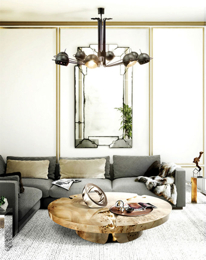A contemporary eclectic living room. It features a modular grey sofa, a rustic coffee table an Art Deco black chandelier and a statement mirror in the background. Image by DelightFULL.