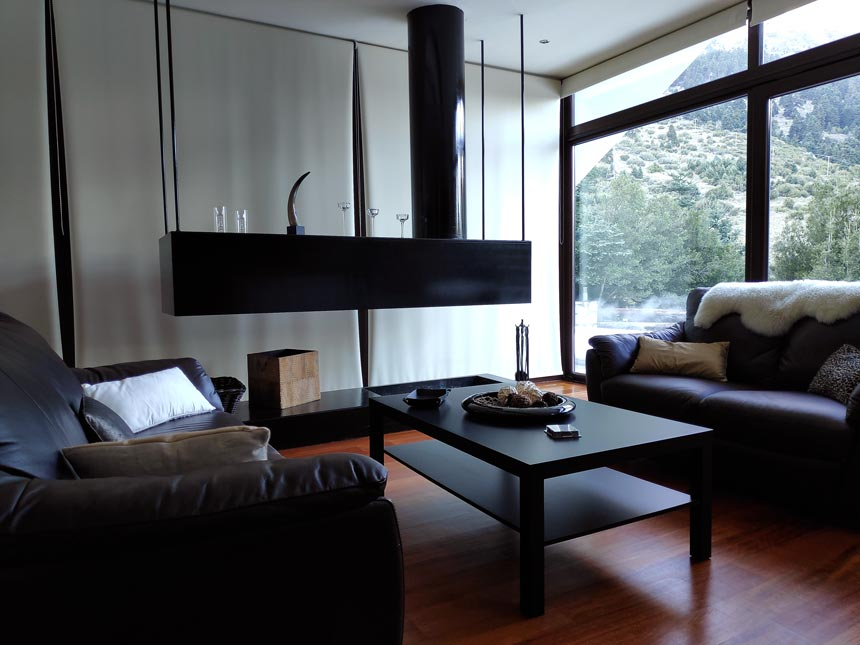 View of the minimal living room with its open fireplace, outdoor views to the forest and leather sofas.