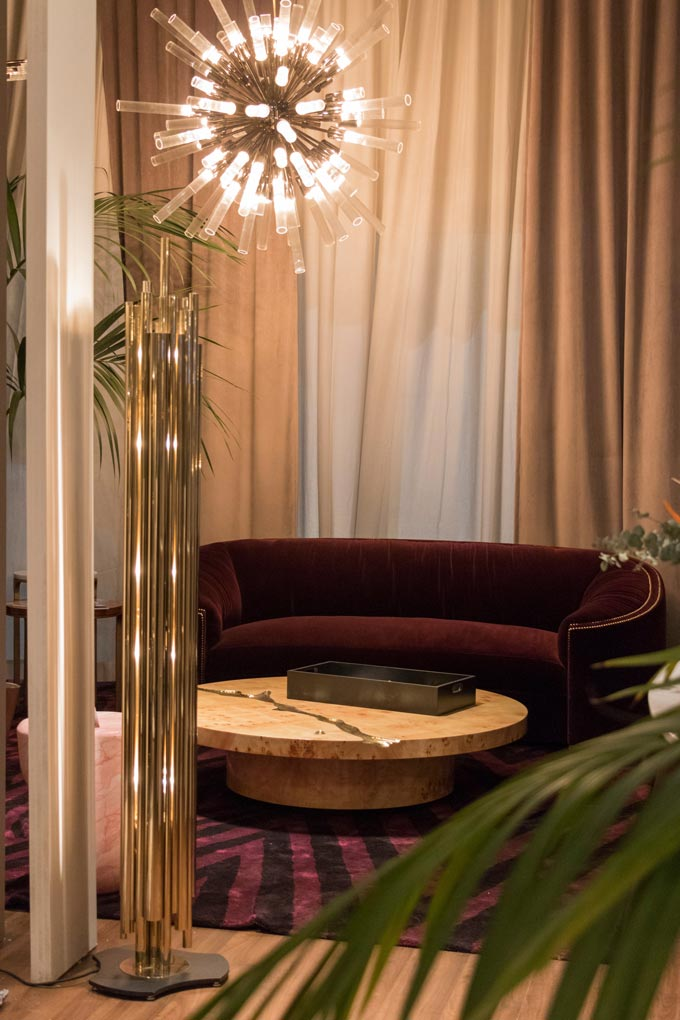 A gorgeous deep burgundy velvet curved sofa with a round coffee table at the Covet House stand at Maison et Objet Paris. Image by Covet House.