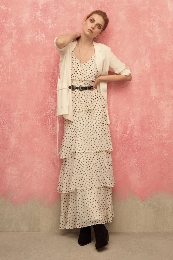 A soft frilled maxi dress in off white with small black polka dots and a black belt around the waist looks so elegant. She's wearing it with black boots and an off white cardigan. Image by Dorothy Perkins.