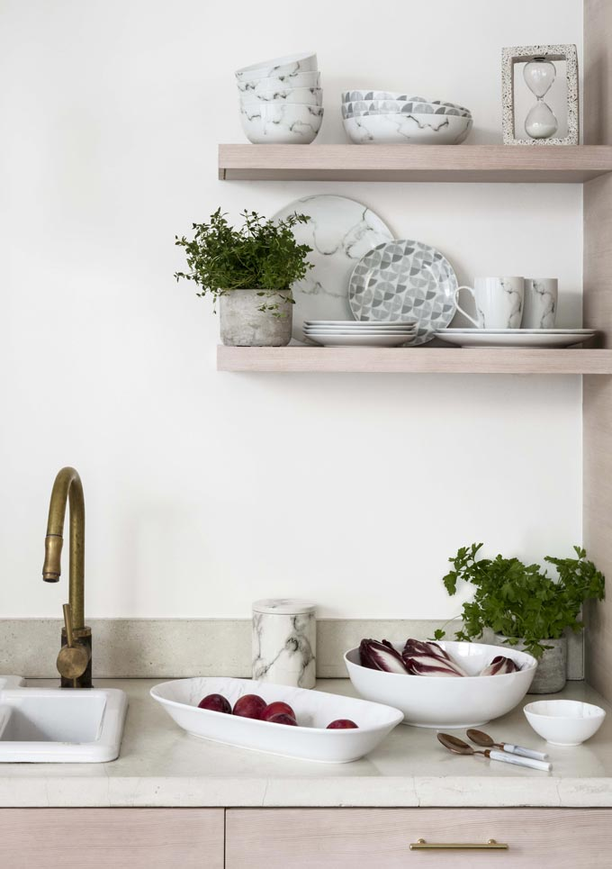 Partial view of a kitchen sink with two small open shelves on the right. Image by George Home.