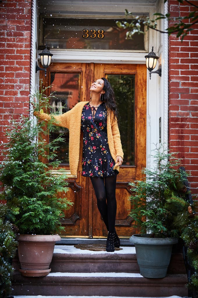 A black floral short dress paired with opaque black tights and ankle boots plus an ochre yellow shawl cardigan looks like a great idea even in the middle of winter. Image by Matalan.