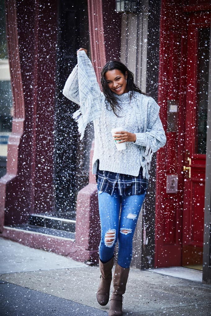 I love a great casual outfit like that - a white textured sweater over of navy check flannel shirt, some distressed denims and knee high boots. So what if it's snowing?! Image by Matalan.