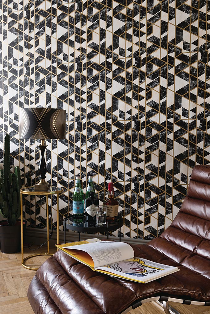 A stunning Art Deco inspired wallcovering with a brown leather chaise in front. Image by MindTheGap.