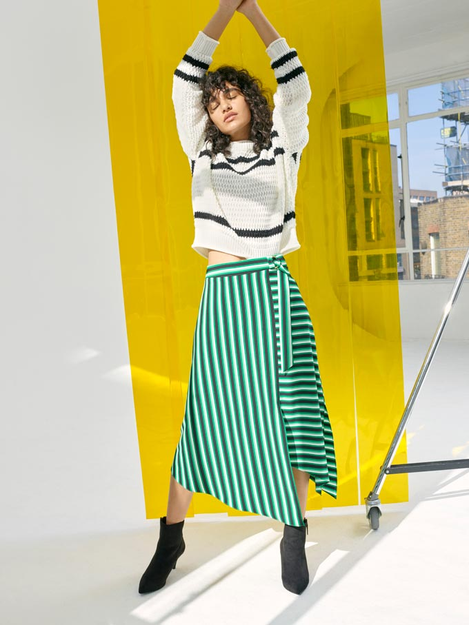 A clash of stripes. A white sweater with black horizontal stripes clashes against a long wrap green skirt with vertical white stripes. They're paired with some black ankle boots. Image by Miss Selfridge.