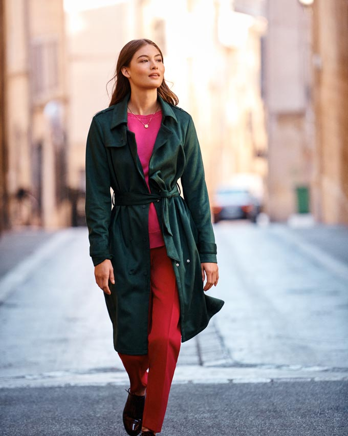 That's a fantastic looking outfit - a forest green sage trench coat over dark pink sweater and red pants. She looks stunning in a simple way. Image by Next.